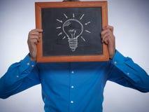 拿着有一个电灯泡的商人一个小黑板对此 库存图片