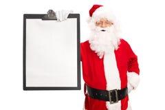 拿着有一个白纸的圣诞老人一张剪贴板 库存照片