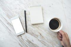 拿着有一个白色手机的手咖啡杯有空白的桌面屏幕和空的笔记本的在桌上 库存照片