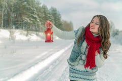 拿着有一个蜡烛的围巾的美丽的年轻深色的妇女红色圣诞节灯笼 免版税图库摄影