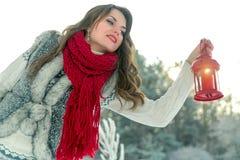 拿着有一个蜡烛的围巾的美丽的年轻深色的妇女红色圣诞节灯笼 免版税库存图片