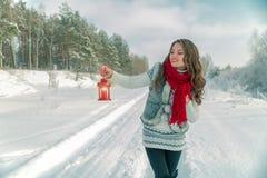 拿着有一个蜡烛的围巾的美丽的年轻深色的妇女红色圣诞节灯笼 免版税库存照片