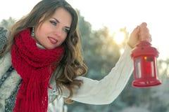 拿着有一个蜡烛的围巾的美丽的年轻深色的妇女红色圣诞节灯笼 库存图片