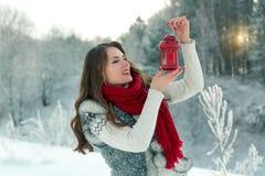 拿着有一个蜡烛的围巾的美丽的年轻深色的妇女红色圣诞节灯笼 库存照片
