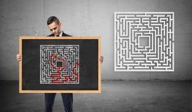 拿着有一个解决的迷宫的图片的商人一个黑板,茫然在他后的一个新的迷宫 免版税库存照片
