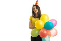 拿着有一个锥体的美丽的女孩很多气球在她头和微笑 免版税图库摄影