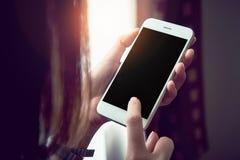 拿着有一个黑屏幕的妇女一个白色电话 葡萄酒作用 图库摄影