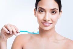 拿着有一些牙膏的微笑的妇女一把牙刷对此 库存照片