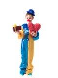 拿着有一把弓的小丑衣服的小男孩一个箱子在一只手和大红色心脏在另一只手上 免版税库存图片