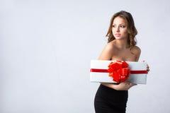 拿着有一条红色弓和丝带的一件黑礼服的妇女白色箱子 免版税图库摄影