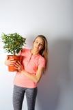 拿着有一棵小中国柑桔树的年轻美丽的妇女一个罐 免版税库存照片