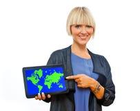 拿着有世界地图的可爱的白肤金发的妇女片剂 免版税库存照片