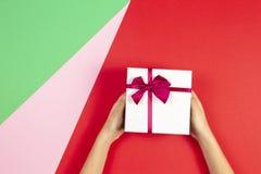 拿着有丝带的孩子手当前礼物盒在红色绿色和桃红色背景 与圣诞节,母亲的祝贺 免版税图库摄影