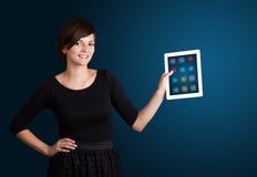 拿着有五颜六色的图标的妇女现代片剂 免版税图库摄影