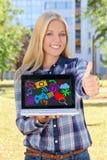 拿着有五颜六色的媒介象和app的美丽的妇女膝上型计算机 免版税库存图片