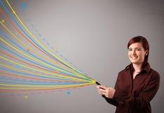 拿着有五颜六色的抽象线路的愉快的女孩一个电话 免版税库存照片