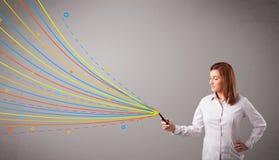 拿着有五颜六色的抽象线路的愉快的女孩一个电话 库存图片