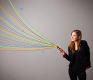 拿着有五颜六色的抽象线路的愉快的女孩一个电话 免版税图库摄影