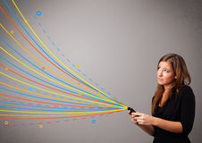 拿着有五颜六色的抽象线路的愉快的女孩一个电话 免版税库存图片