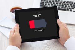 拿着有低落的男性手片剂在屏幕充电了电池 免版税库存图片