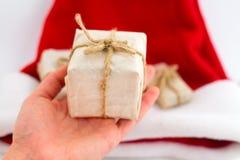 拿着有作为一个礼物的手工艺纸礼物盒圣诞节的,在白色背景的新年,顶视图 免版税图库摄影