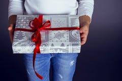 拿着有假日礼物的美丽的小女孩一个箱子 免版税库存图片