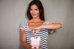 拿着有储款的愉快的妇女存钱罐 免版税图库摄影