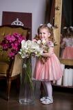 拿着有兰花和微笑的一件桃红色礼服的蓝眼睛的逗人喜爱的女孩一个花瓶 库存照片