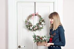 拿着有冷杉的少妇圣诞节木箱在假日分支 庆祝新年度 库存图片