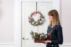 拿着有冷杉的少妇圣诞节木箱在假日分支 庆祝新年度 图库摄影
