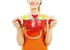 拿着有准备好膳食的,汤的围裙的主妇平底锅 免版税库存图片