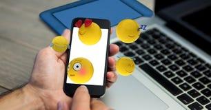 拿着有各种各样的emojis的手特写镜头手机在木桌上 库存例证