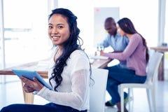 拿着有同事的年轻女实业家画象片剂个人计算机在背景中 库存照片