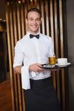 拿着有咖啡杯和品脱的微笑的侍者盘子啤酒 库存照片