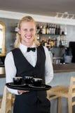 拿着有咖啡杯的侍者一个盘子在餐馆 免版税库存图片