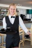 拿着有咖啡杯的侍者一个盘子在餐馆 图库摄影