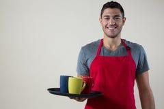 拿着有咖啡杯的微笑的侍者一个盘子 免版税库存图片