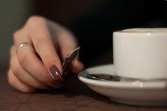 拿着有咖啡热奶咖啡的特写镜头女性手杯子与泡沫 免版税库存照片