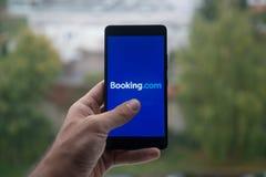 拿着有售票的人智能手机 与手指的com商标在屏幕上 库存照片