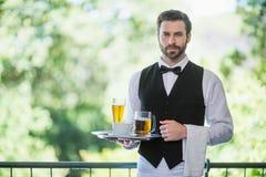 拿着有啤酒杯和咖啡杯的男性侍者盘子在餐馆 免版税库存图片