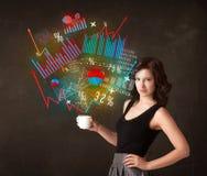 拿着有图和图表的女实业家一个白色杯子 库存图片