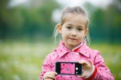 拿着有图片的小女孩一个巧妙的电话在显示 免版税库存照片