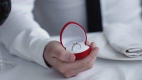 拿着有圆环做的人的关闭箱子提议给他的女朋友,餐馆 免版税库存照片