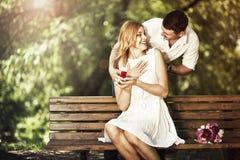 拿着有圆环做的人红色箱子提议给他的女朋友 免版税库存照片