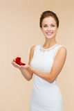 拿着有圆环的微笑的妇女红色礼物盒 图库摄影