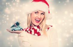拿着有圣诞树的妇女小汽车 免版税库存图片