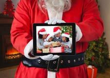 拿着有圣诞节家庭照片的圣诞老人一种数字式片剂  免版税库存图片