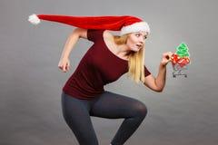 拿着有圣诞节礼物的圣诞老人妇女购物车 免版税库存照片