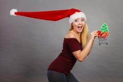 拿着有圣诞节礼物的圣诞老人妇女购物车 免版税图库摄影