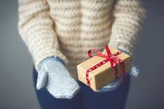 拿着有圣诞节礼物的女孩一个箱子 免版税库存图片